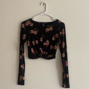 Long sleeve black crop top with floral print.